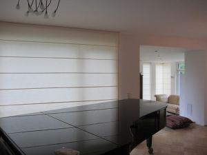 Cascade Roman shades on the window next to the piano