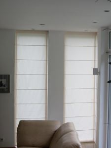 The same type of Roman blinds covering the narrower (fixed) east-facing windows.